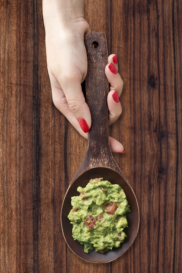Woman holding spoon with guacamole